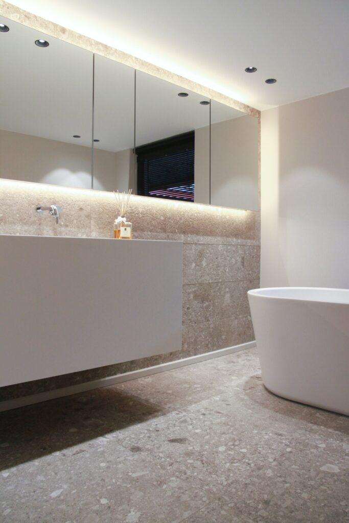 Badezimmer mit Decken- und Spiegelleuchten.